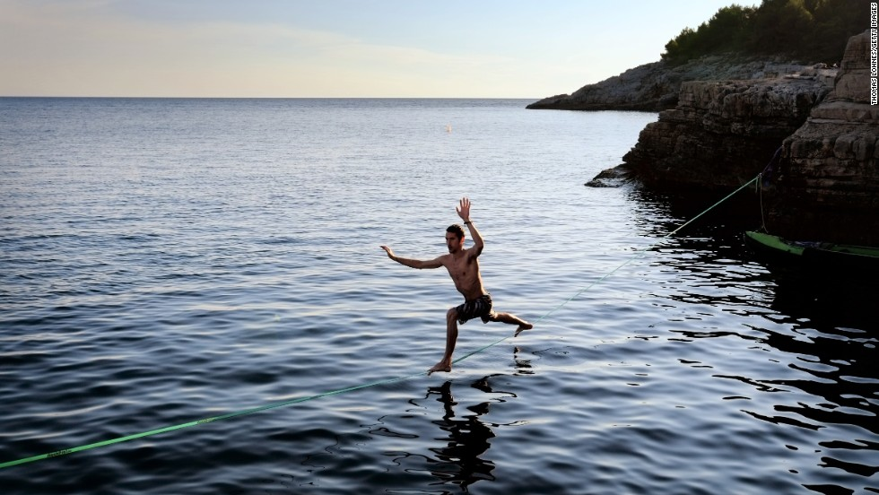 "A man balances on a slackline at the cliffs of Stoja near Pula, Croatia, on Tuesday, August 5. The area is known for ""deep water soloing,"" or free climbing over water."