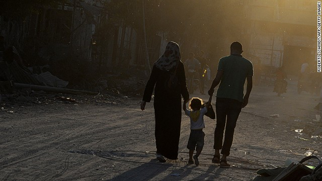 :Sammy Al-Sheikh (R) and his wife Maha (L) hold hands with their three-year-old daughter Assil as they walk past destroyed houses in the devastated neighbourhood of Shejaiya in Gaza City on August 7, 2014. Sammy who lives and works in Gaza City expressed hopes for peace and said peace would allow him to return to work. Fears rose that the Gaza conflict could resume as a temporary ceasefire entered a final 12-hour stretch and Palestinians accused Israel of stalling at truce talks in Cairo. AFP PHOTO/ROBERTO SCHMIDT (Photo credit should read