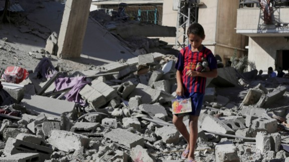 A Palestinian boy salvages family belongings from the rubble of a four-story building after an airstrike in Gaza City on Friday, August 8.