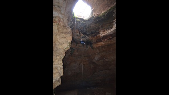 Justin Sipla ascends a rope dangling from 80 feet after working at the bottom of the cave.