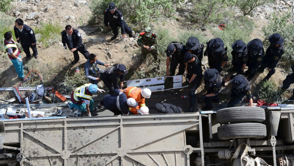 Rescuers work to pull victims from an overturned tour bus after it fell off a cliff in Nyemo County, Tibet, on Saturday, August 9.