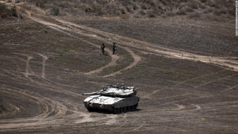Israeli soldiers walk past a Merkava tank as they patrol a field near Israel's border with Gaza on August 9.
