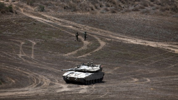 Israeli soldiers walk past a Merkava tank as they patrol a field near Israel
