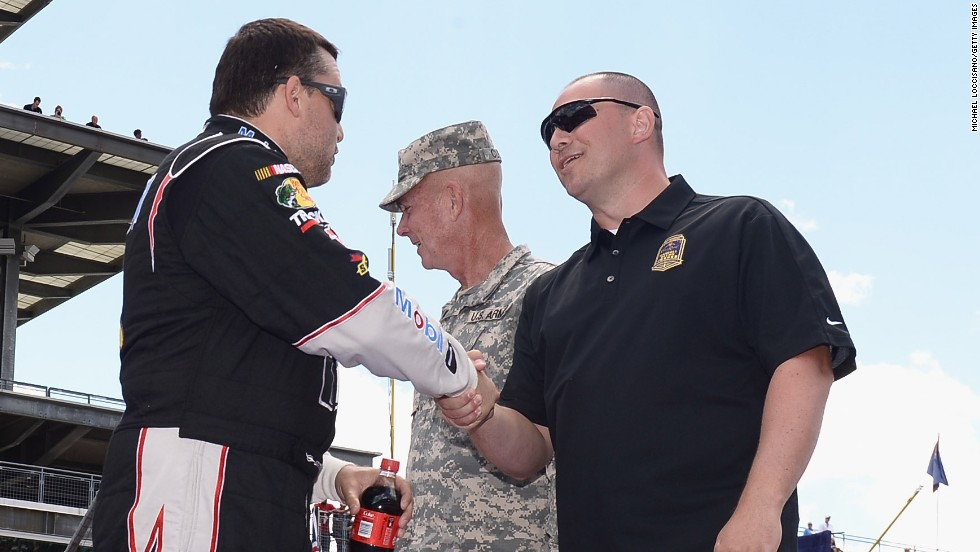 Stewart shakes hands with a member of the military at the Indianapolis Motor Speedway in July 2013.