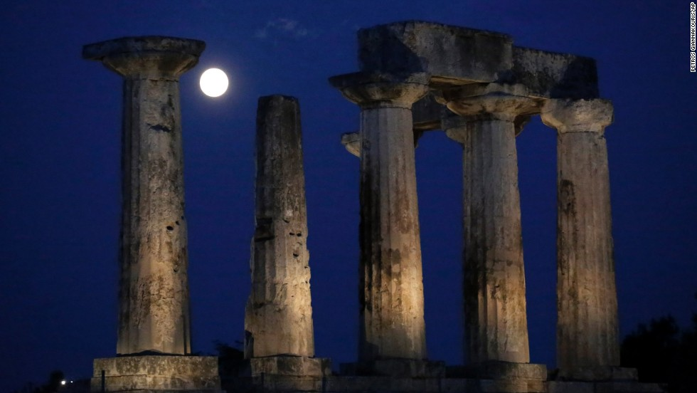 The moon appears behind Apollo's Temple at ancient Corinth, southwest of Athens, Greece.