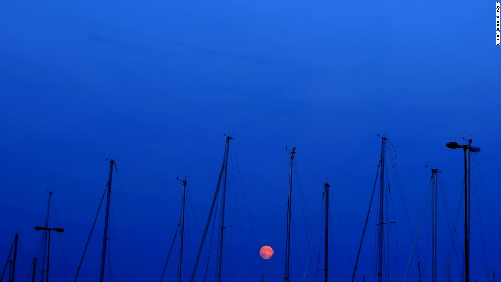 The moon is seen among the masts of sailing boats in Fiskeback Harbor, outside of Gothenburg, Sweden.