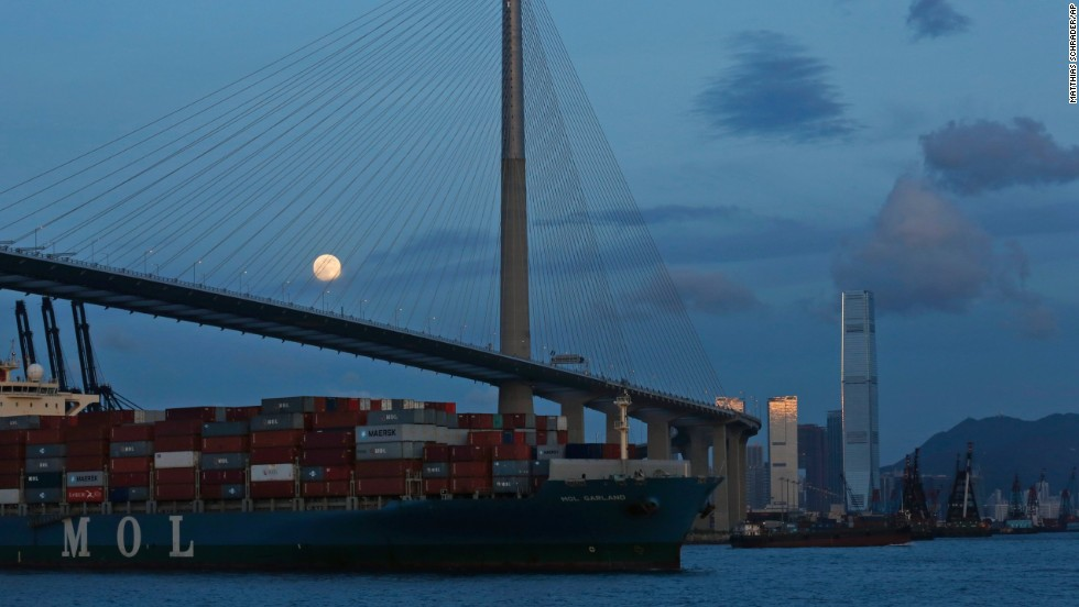 The moon provides a backdrop for a bridge in Hong Kong.