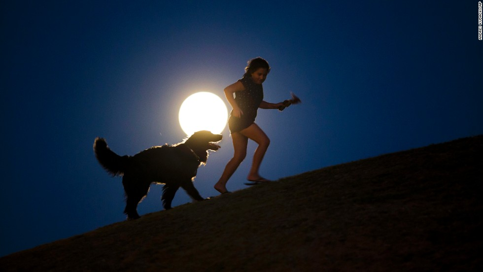 A girl plays with a dog in the light of the moon in Madrid, Spain.