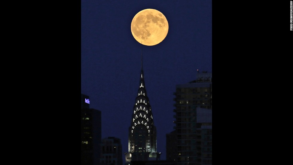 The moon appears over the New York skyline in a view from Weehawken, New Jersey, on August 10.