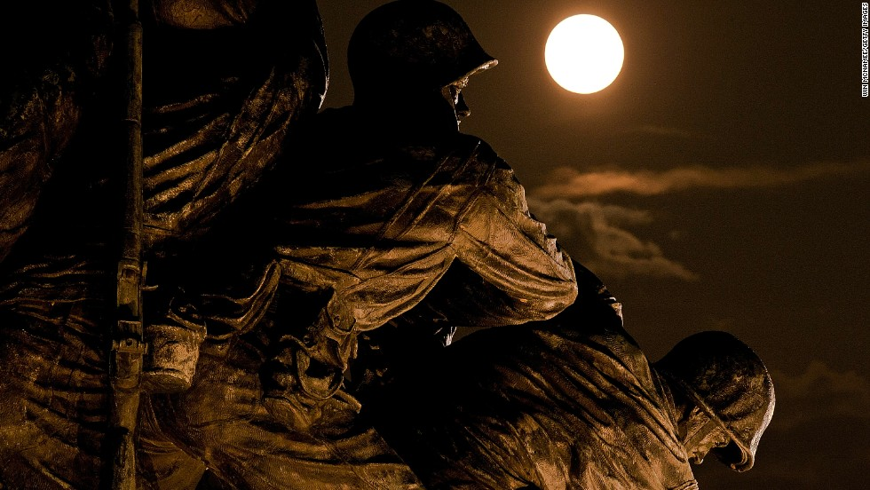 The moon rises above the U.S. Marine Corps War Memorial in Arlington, Virginia.