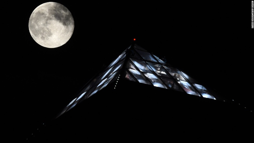 The moon rises behind the light on top of the Luxor Hotel and Casino in Las Vegas.