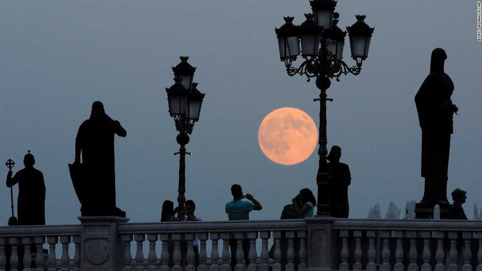 People take photos as the moon rises above a bridge over Vardar River in Skopje, Macedonia.