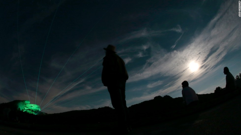 People watch a laser and light show on the Crazy Horse Memorial, left, under a supermoon in Custer, South Dakota.