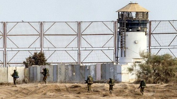 Caption:Israeli soldiers walk past a fence along Israel's border with the Gaza Strip, on August 4, 2014. An eight-year-old girl was killed and 30 people wounded in a strike on the beachfront Shati refugee camp in Gaza City just minutes into an Israeli-declared truce, medics said. AFP PHOTO / JACK GUEZ (Photo credit should read JACK GUEZ/AFP/Getty Images)
