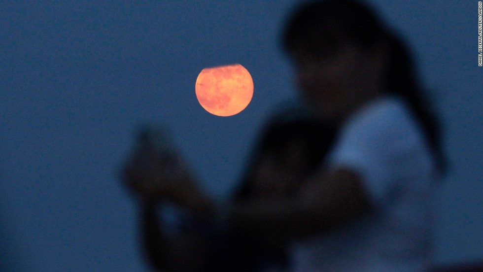 "A <a href=""http://www.cnn.com/2014/08/08/us/irpt-august-supermoon/index.html "">supermoon</a> rises as a mother and daughter take selfies Sunday, August 10, in Monterrey, Mexico. Supermoons happen when the moon becomes full on the same day as its perigee -- the point in the moon's orbit when it's closest to Earth. Full moons occur near perigee approximately every 13 months, according to NASA."