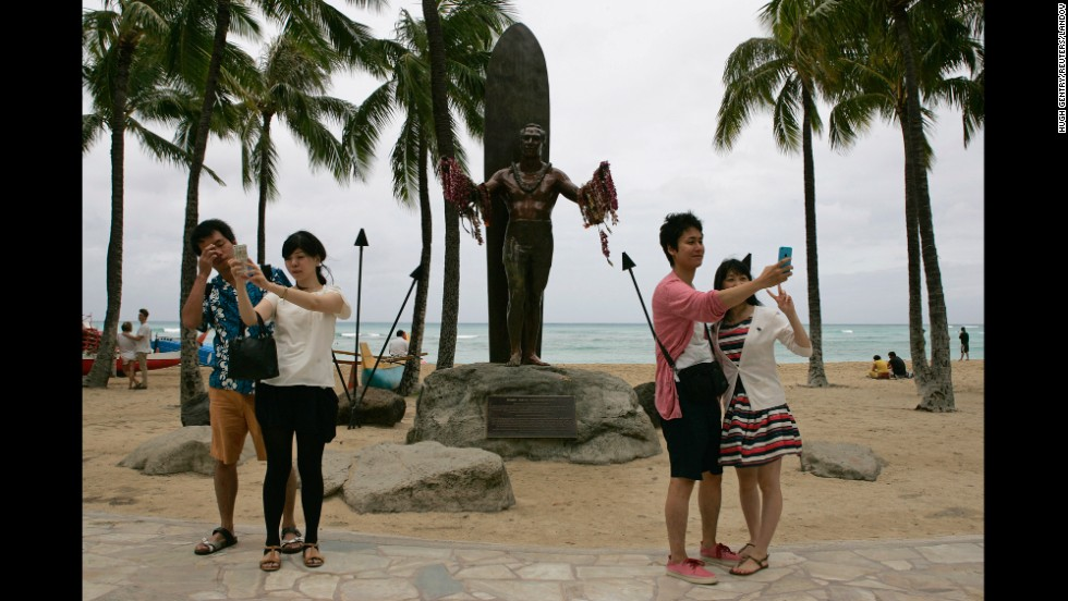 "Tourists take selfies in front of the Duke Kahanamoku statue in Honolulu on Friday, August 8. Kahanamoku was an Olympic gold medalist in swimming who is credited with bringing surfing to the outside world. <a href=""http://www.cnn.com/2014/08/06/world/gallery/look-at-me-0806/index.html"">See 18 selfies from last week</a>"