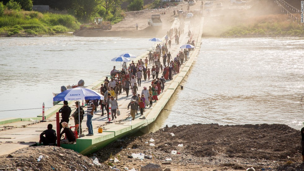 Thousands trudge across a river to seek humanitarian aid in Syria.