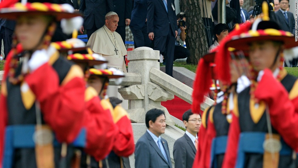 Pope Francis walks down stairs during a welcoming ceremony in Seoul.