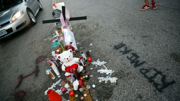 A makeshift memorial sits in the middle of the street on Monday, August 11, where Michael Brown was shot and killed.
