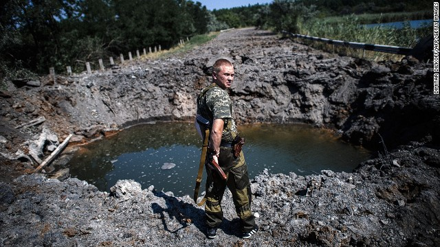 A pro-Russian gunman stands next to a bomb crater after shelling near Donetsk on Thursday.