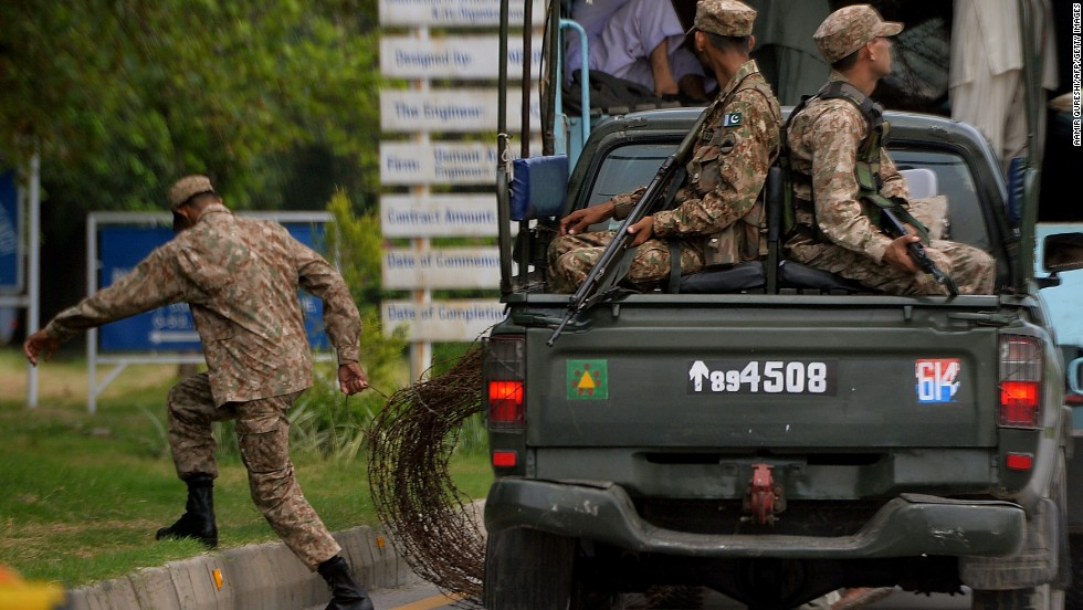 "Soldiers roll out barbed wire as they patrol the ""red zone"" area of Islamabad on August 13."