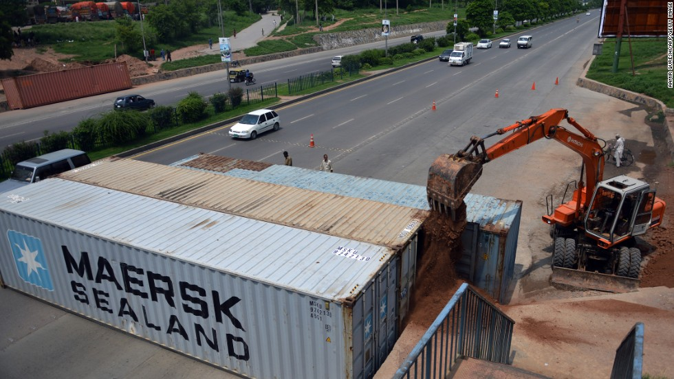An excavator shifts sand into shipping containers placed by security forces as roadblocks on a street in Islamabad on August 13.