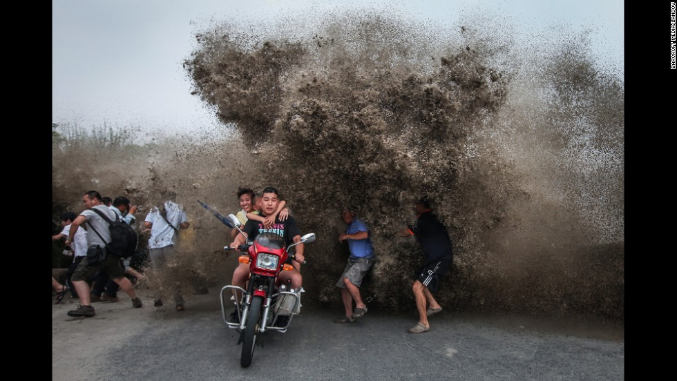 People run as a high wave hits the Qiantang River bank Wednesday, August 13, in Hangzhou, China.