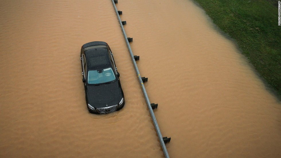 A partially submerged car sits on a flooded section of Interstate 695 in Baltimore on Tuesday, August 12, after heavy rains fell across the Mid-Atlantic region of the United States.