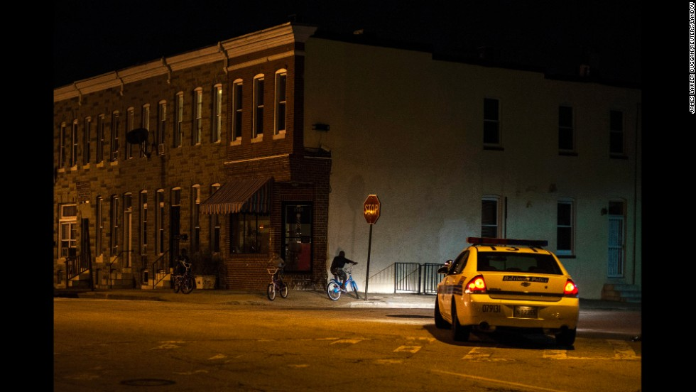 "Police patrol a residential neighborhood in east Baltimore minutes after a new curfew law took effect Friday, August 8. Mayor Stephanie Rawlings-Blake said the measure is aimed at getting children off the streets before they are put in danger. <a href=""http://www.cnn.com/2014/08/08/world/gallery/week-in-photos-0808/index.html"">See last week in 34 photos</a>"