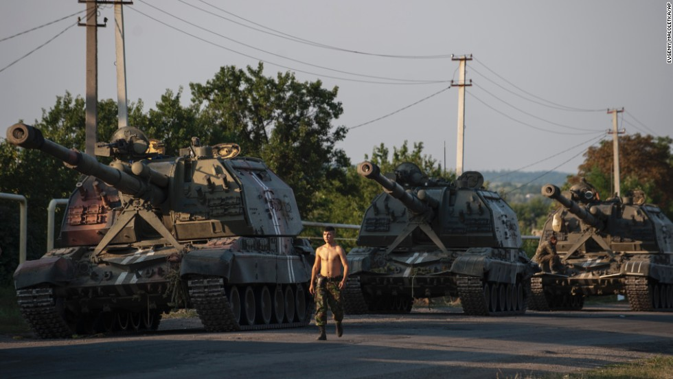 A Ukrainian soldier walks past a line of self-propelled guns as a column of military vehicles prepares to head to the front line near Ilovaisk on Thursday, August 14.