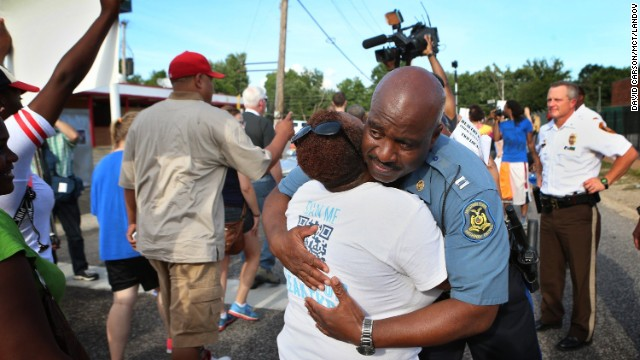 Missouri State Highway Patrol Capt. Ron Johnson gets a hug from Angela Whitman as protesters march on  Aug. 14.