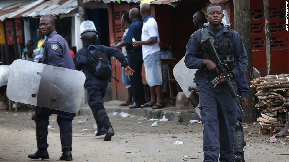Liberian police depart after firing shots in the air while trying to protect an Ebola burial team in the West Point slum of Monrovia on August 16, 2014. A crowd of several hundred local residents reportedly drove away the burial team and their police escort. The mob then forced open an Ebola isolation ward and took patients out, saying the Ebola epidemic is a hoax.