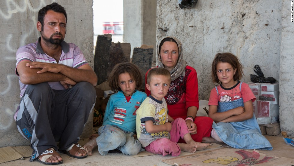 Instantly made homeless, tens of thousands of Yazidi families have sought shelter in Iraqi Kurdistan after being chased from their homes, often at gunpoint, by ISIS.  Kurdish photographer Warzer Jaff spent a week documenting the exodus of the Yazidis from their ancient homeland. This portrait shows the family of former soldier Hajji Khalaf, 28, from Sinjar.  With him is daughter Alisa, 3; son Ezel, 4; wife Thawra, 24; and daughter Alifa, 6.