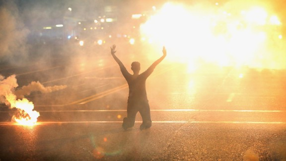 Tear gas reigns down on a woman kneeling in the street with her hands in the air after a demonstration over the killing of teenager Michael Brown by a Ferguson police officer on August 17, 2014 in Ferguson, Missouri. Despite the Brown family's continued call for peaceful demonstrations, violent protests have erupted nearly every night in Ferguson since his August 9, death.