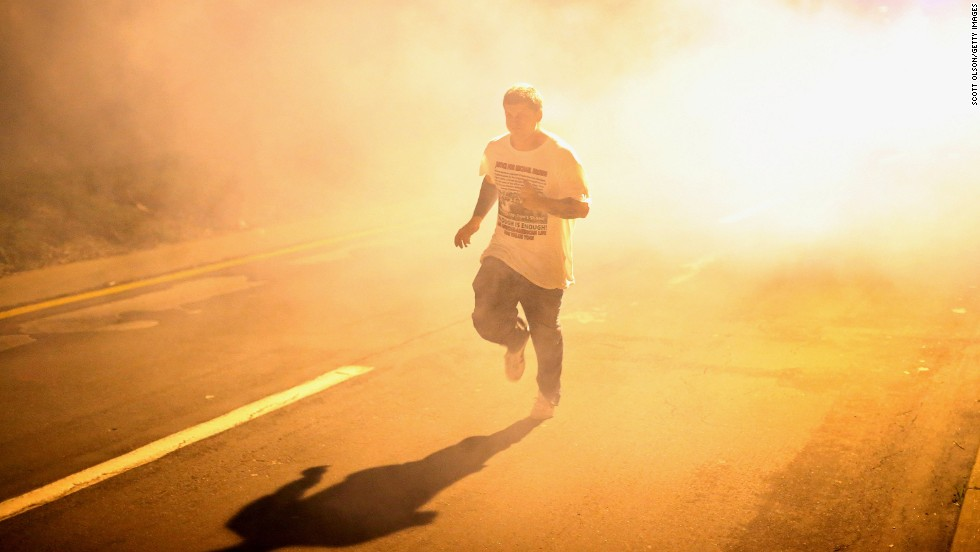 A man runs through clouds of tear gas on August 17, 2014.