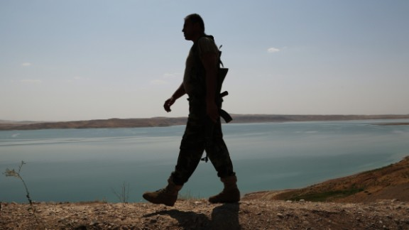 A Kurdish peshmerga fighter patrols near the Mosul Dam outside Mosul, Iraq in August.