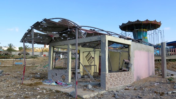 The amusement park's carousel can be seen next to the shell of a destroyed building.