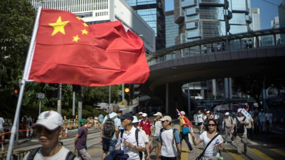 A anti-Occupy Central supporter carry a Chinese national flag during the march on August 17, 2014 in Hong Kong. Organised by the Alliance for Peace and Democracy, the anti-Occupy Central march runs along the route from Victoria Park in Causeway Bay to Chater Road in Central. on August 17, 2014 in Hong Kong, Hong Kong. (Photo by Lam Yik Fei/Getty Images)