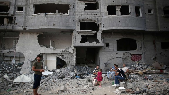 Palestinians sit in their destroyed neighbourhood in the northern Gaza Strip city of Beit Hanun, on August 18, 2014. Prime Minister Benjamin Netanyahu warned that Israel will hit back hard if Palestinian rocket attacks from Gaza resume, speaking just hours before the midnight expiry of a five-day ceasefire. AFP PHOTO / THOMAS COEXTHOMAS COEX/AFP/Getty Images