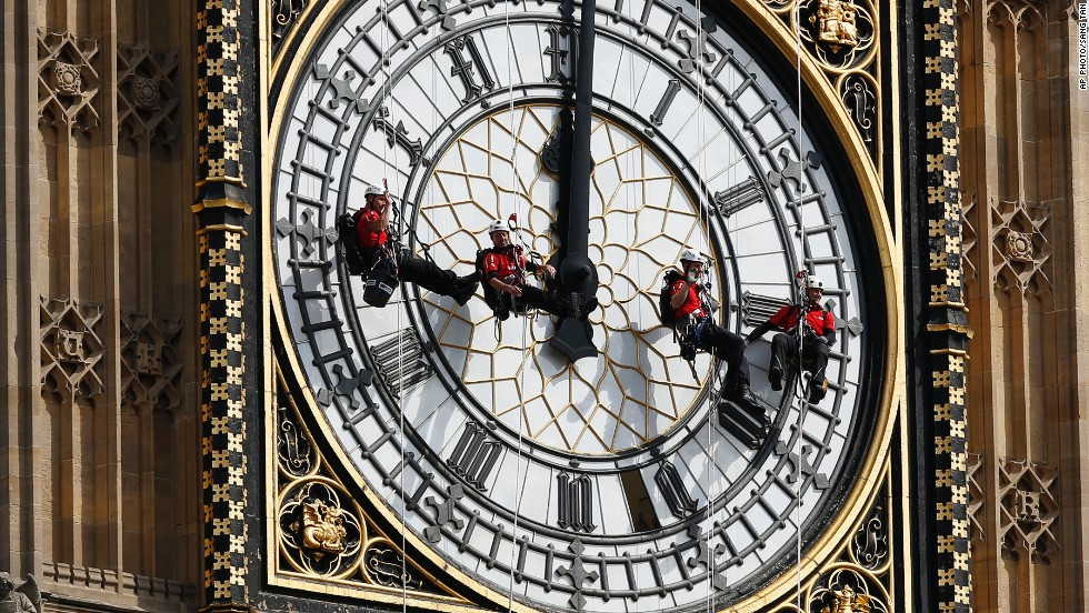 "AUGUST 18 - LONDON, ENGLAND: Workers hang in front of the clock face of Big Ben as they clean the city's landmark timepiece at the Houses of Parliament in Westminster. <a href=""http://cnn.com/2013/10/15/world/europe/big-ben-fast-facts/"">The name ""Big Ben"" originally referred to just the bell of the clock,</a> but has also come to indicate the clock, the tower and the bell."