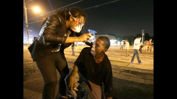 A woman helps a man affected by tear gas August 18, 2014. The situation overnight deteriorated after a handful of protesters threw rocks, bottles and Molotov cocktails at police. Officers responded by firing stun grenades and tear gas canisters.