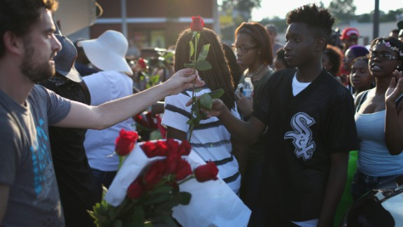 Demonstrators receive red roses as they protest August 18, 2014.