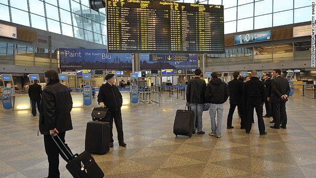 Passengers gather beside an information board at Helsinki Airport on April 16, 2010, following the cancellation of flights. Flight restrictions due to ash from an Iceland volcano have been extended across Finland and are expected to last 'several days', airport operator Finavia said