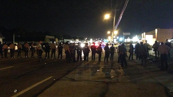 Line of police march wall to wall in Ferguson to clear main drag.
