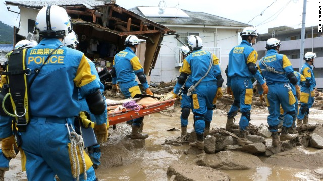 A troop of police rescue personnel head out for rescue operation after a massive landslides swept through residential area in Hiroshima, western Japan, Wednesday, Aug. 20, 2014.