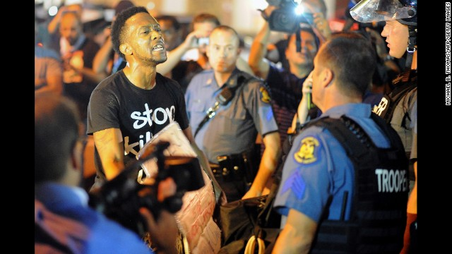 A protester speaks to a police officer on August 19.