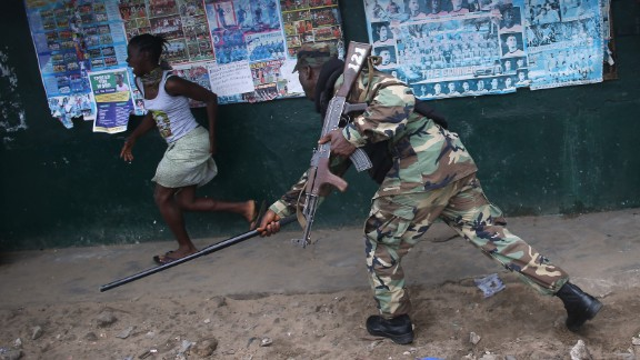 An Ebola Task Force soldier beats a local resident while enforcing a quarantine on the West Point slum on August 20, 2014.