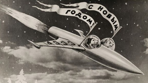 """This postcard (1960), by the photomontage artist Sveshnikov, shows the dogs Belka and Strelka in their rocket. The flags read """"Happy New Year""""."""