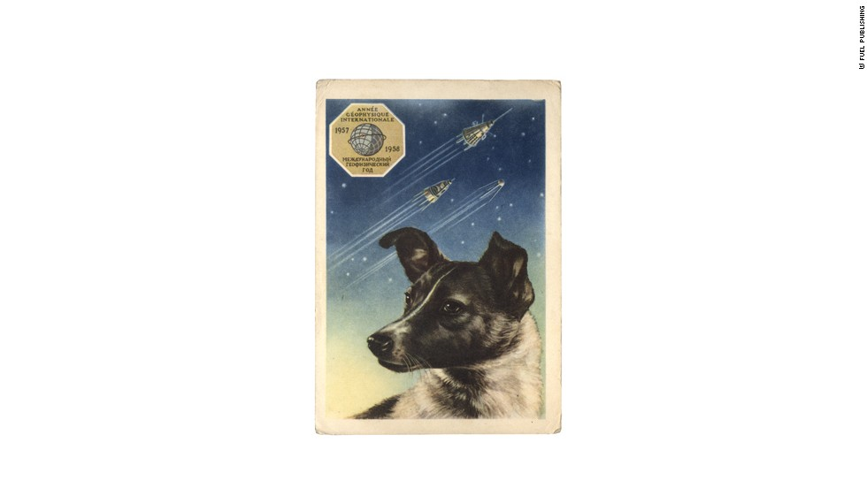 Laika became a national treasure, a sort of martyr for the USSR. As such, the celebrity dog would appear on a range of posters, toys and stamps. This is a portrait of Laika on a postcard (1958) by the artist E. Gundobin, with the first three Sputniks in the background. <br />