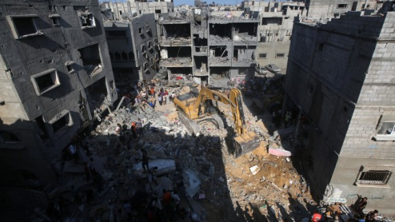 Palestinian emergency personnel dig through the rubble of a building destroyed in an Israeli military strike in Rafah in the south of Gaza on August 21, 2014.